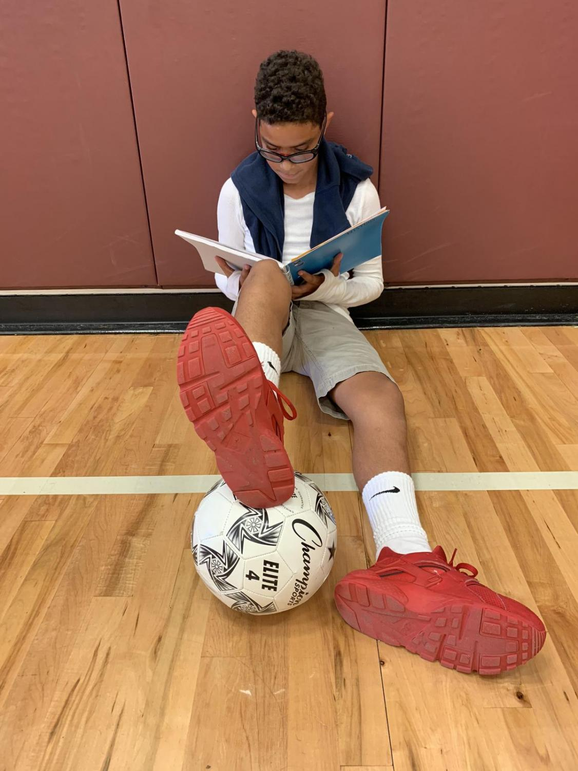 6th grader, Jedriel Perez, studying notes in the gym before he plays soccer.