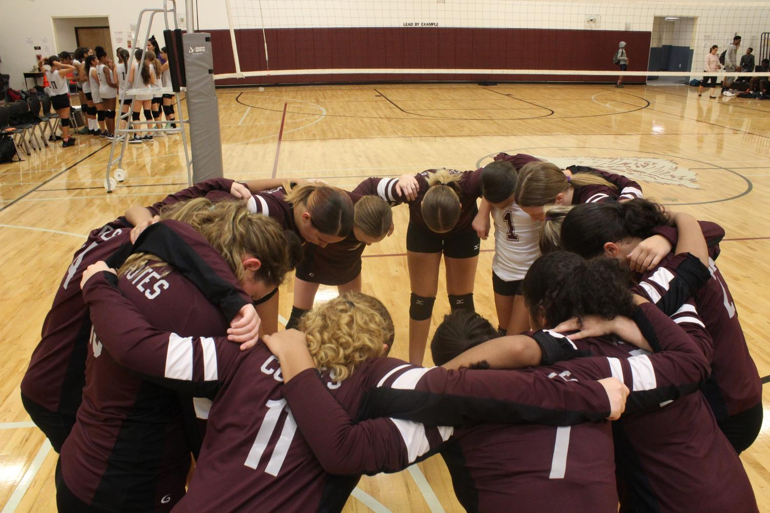 Middle school volleyball team huddled together for a pregame pep talk a few moments before the game against Tapestry begins.