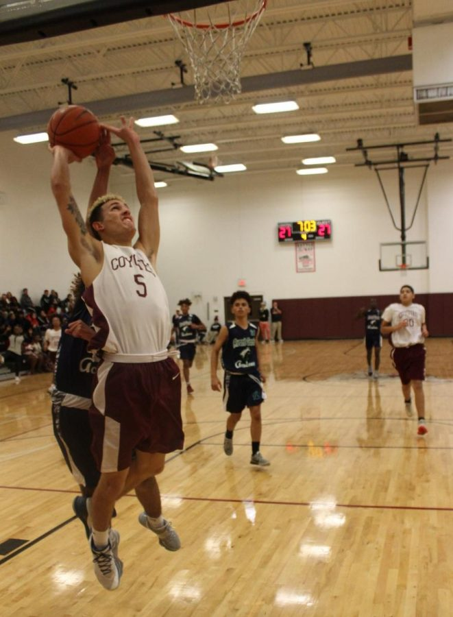 Junior Miguel Fonseca plays through the contact on a strong two handed layup.