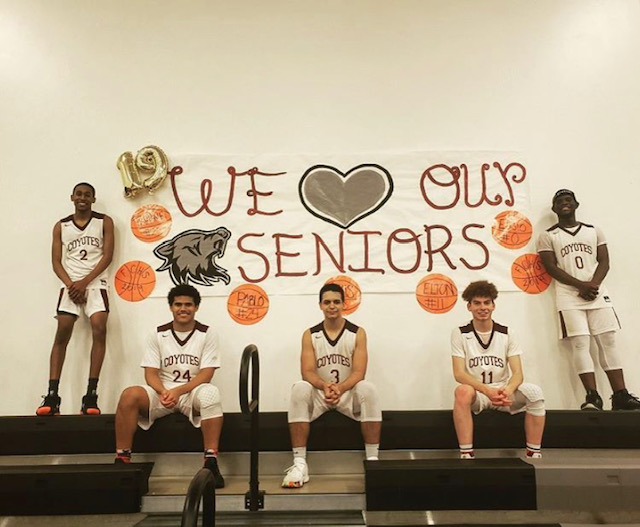 The+senior+basketball+players+pose+for+a+picture+next+to+the+banner+made+by+SGA.