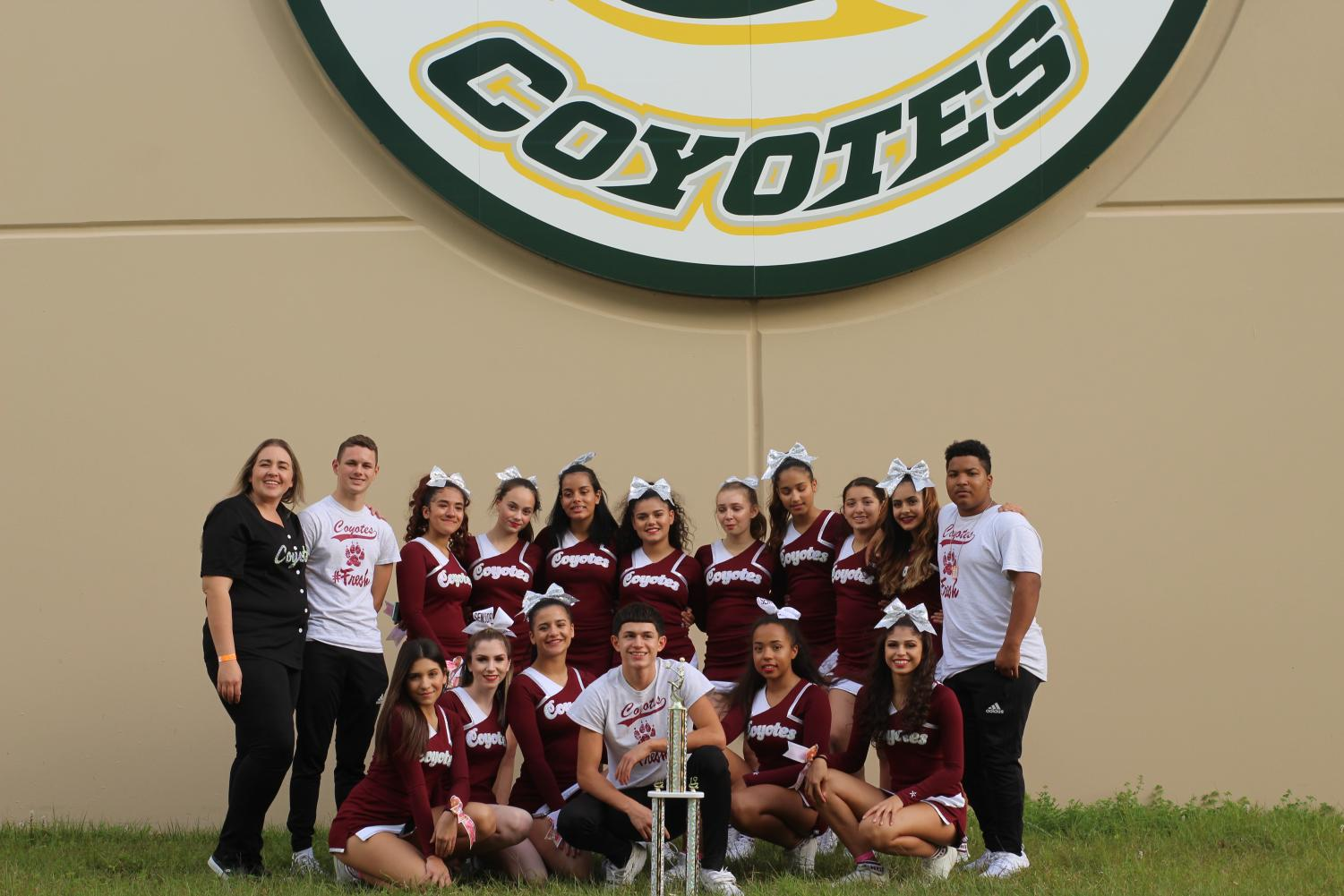 The Cheer squad poses with the 1st place trophy after their victory.