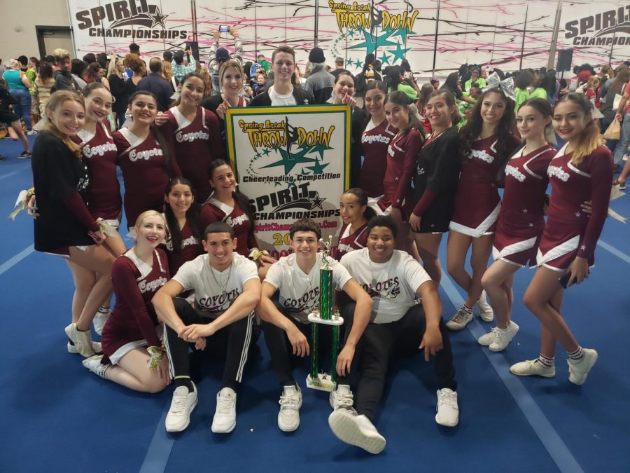 Coyote cheer squad poses in front of trophy.