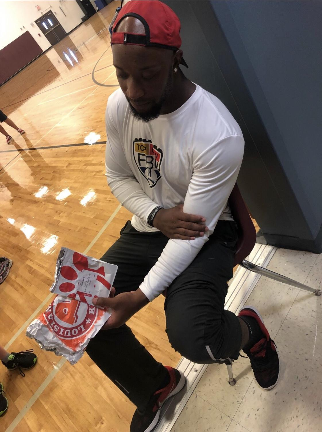 Coach Mike Jones shows off his love of Popeyes and Chick-Fil A sandwiches.