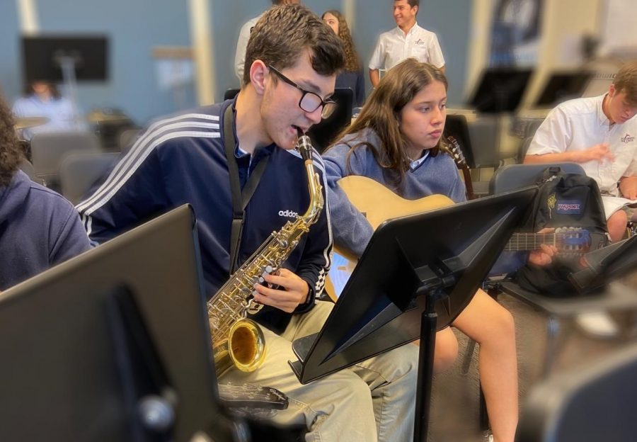 Band member, junior, Ryan Taylor rehearses as a part of the band, which will be performing the school song.