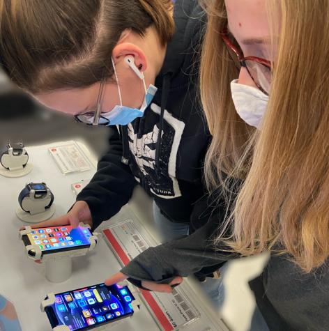 Freshman, Ashlie VanGilder, and seventh grader Meghan VanGilder checking out the new iPhone 12 models.