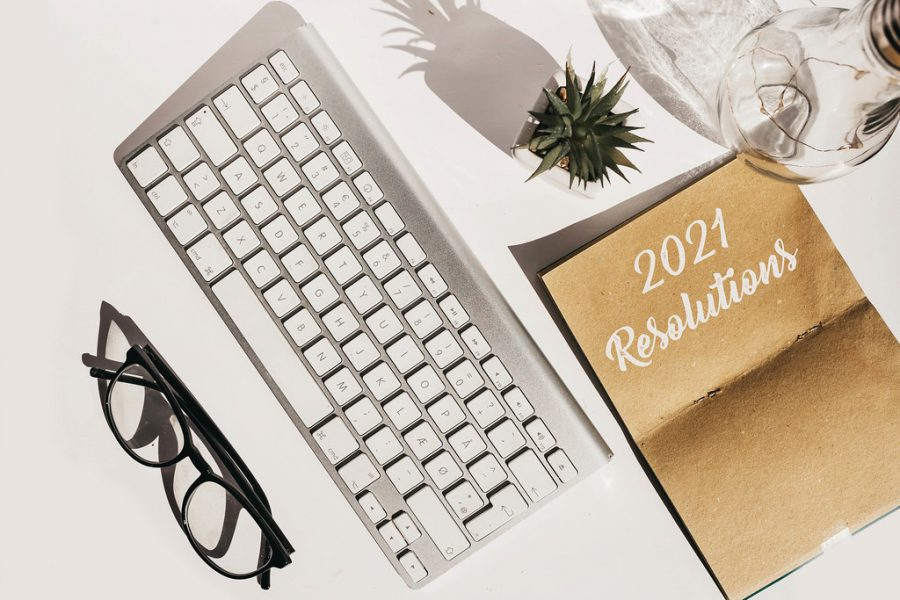 Top view of flat lay with keyboard, glasses, plant and notebook with 2021 goals. New year resolution. by wuestenigel is licensed under CC BY 2.0
